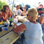 People eating and talking at picnic table